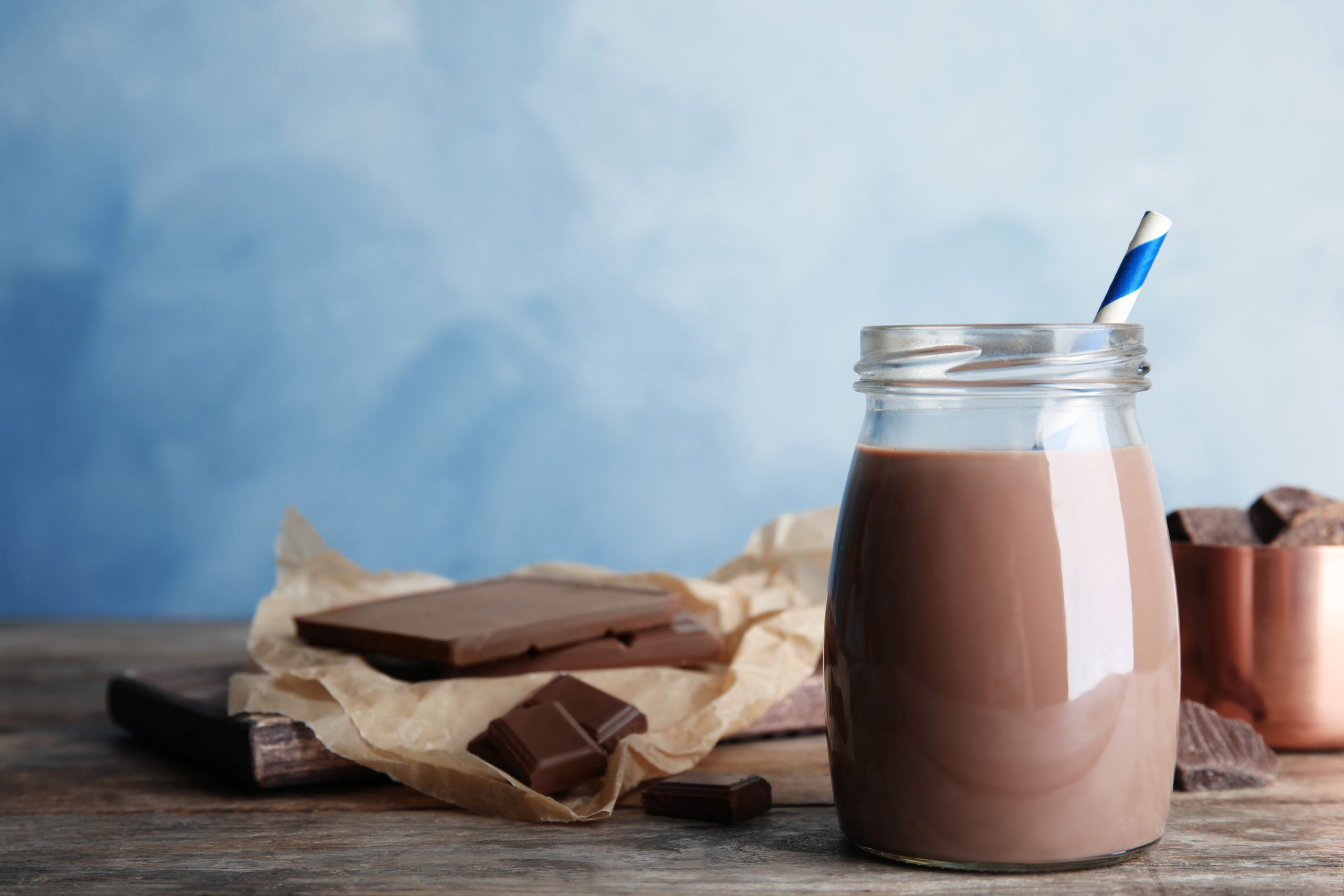 Jar with tasty chocolate milk on wooden table, space for text. Dairy drink