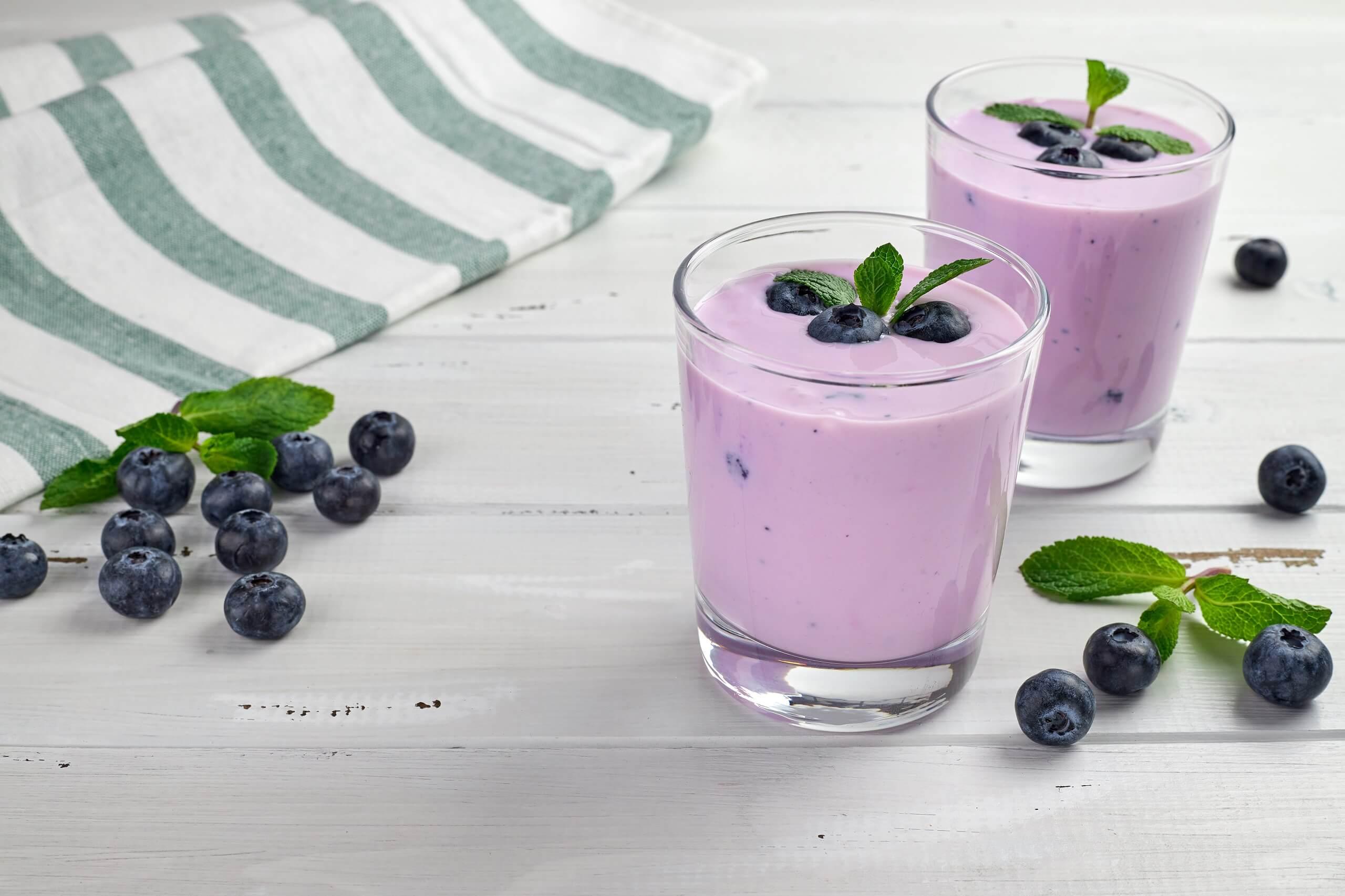 blueberry-yogurt-served-with-fresh-blueberries-mint-leaves-two-glasses-yogurt-white-wooden-table-healthy-breakfast